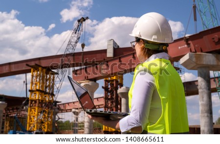 Female foreman working on laptop at bridge construction site. Girl builder controls erection of car road.