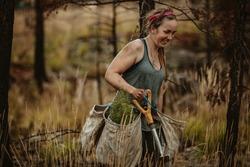 Female forest ranger planting new trees. Forester walking through dry grass carrying bag full of new seedlings and shovel.