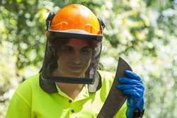 female forest worker or lumberjack with ax to cut trees in forest