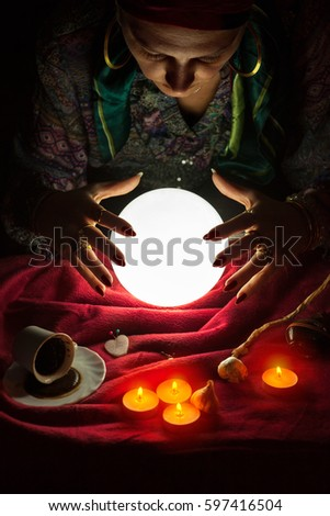 Female fortuneteller with her hands above lighted crystal ball #597416504