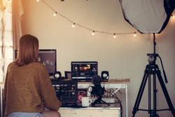 Female freelance editor working editing video footage with laptop in house studio this is lifestyle of blogger or content creator freelance