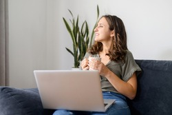 Female freelancer daydreaming with a cup of morning coffee, smiling woman sits on the couch with a laptop, looks away, waiting for inspiration or new ideas