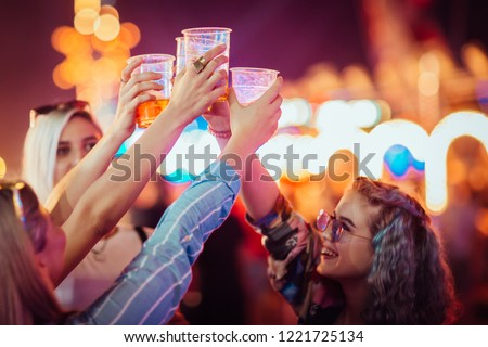 Female friends cheering with beer at music festival #1221725134