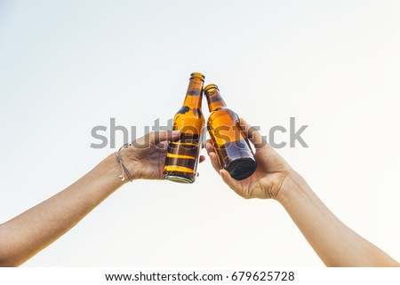 Female friends cheers clinking bottles of beer in hands in the park.