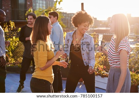 Female friends dancing and drinking at a rooftop party #785100157