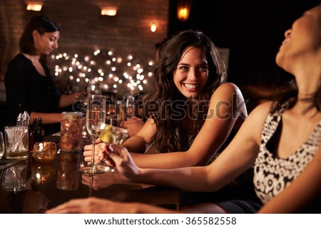 Female Friends Enjoying Night Out At Cocktail Bar #365582558
