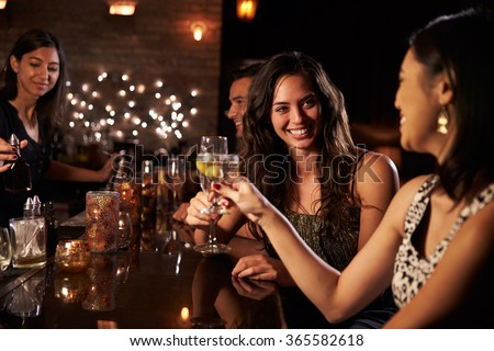 Female Friends Enjoying Night Out At Cocktail Bar #365582618