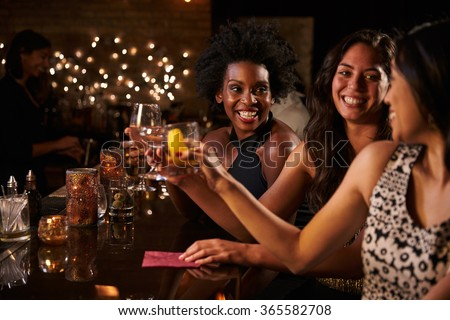 Female Friends Enjoying Night Out At Cocktail Bar #365582708