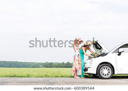 Female friends examining broken down car on country road against clear sky