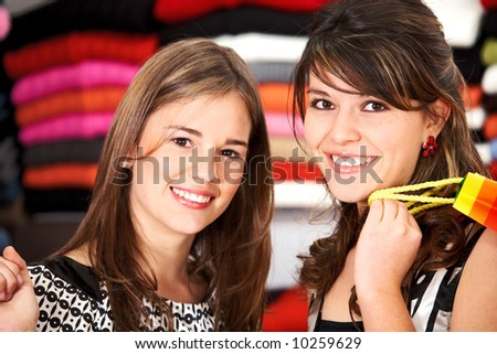 female friends in a retail store smiling and buying some clothes