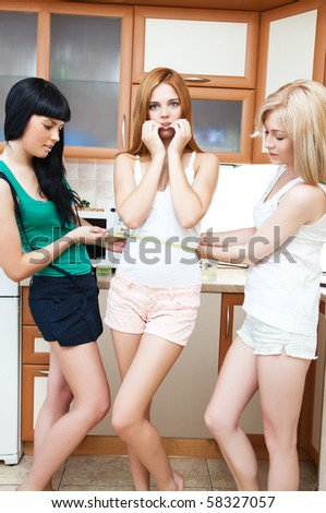 Female friends measuring waist on kitchen.