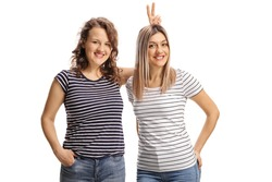 Female friends posing and making bunny ears on head isolated on white background