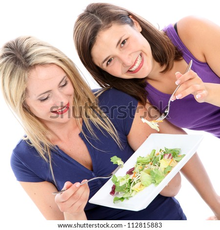 Female friends sharing a plate of salad Two attractive female friends sharing a plate of healthy leafy green salad together isolated on white