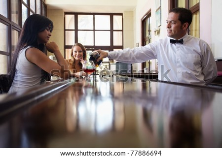 female friends sitting in pub and hispanic barman serving cocktail. Horizontal shape side view, copy space