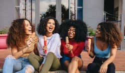 Female friends sitting outdoors enjoying eating ice cream. Group of cheerful girls enjoying ice lollies on a summer day.