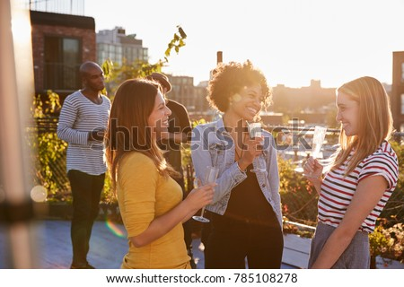 Female friends talking at a rooftop party, backlit #785108278