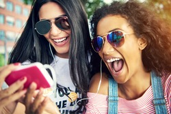 Female friends wearing sun glasses and smile widely as they take a photo with their cell phone