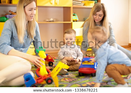 Female friends with babies toddlers playing on the floor in sitting room