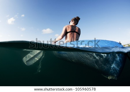 female from behind paddling a kayak on the ocean
