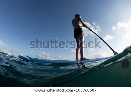 female from behind paddling a paddleboard on the ocean