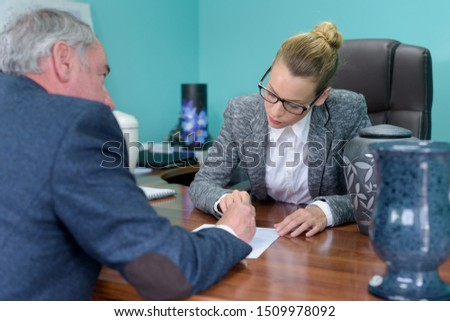 female funeral director completing paperwork with senior man #1509978092