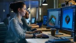 Female Game Developer Works on a Level Design on Her Personal Computer with Two Displays. She works in a Creative Office Space.