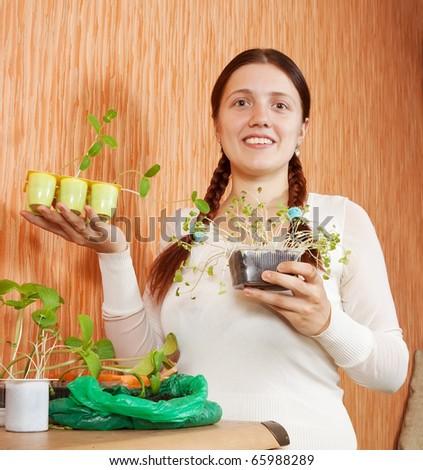Female gardener with various seedlings at home - stock photo