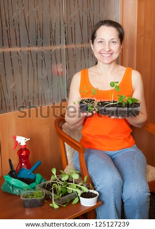 Female gardener with various sprouts at home