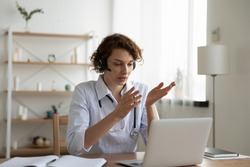 Female general practitioner wears white coat and headset speaking videoconferencing on laptop computer using online video call consultation app. Remote medical help for distance patient, telemedicine.