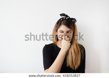 Female gesture smells bad. Portrait of woman wearing casually pinches nose with fingers hands looks with disgust something stinks bad smell situation. Human face expression body language reaction