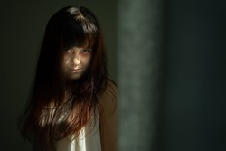 Female ghost in white dress in room. A young scary girl in an old white dress staring in to the camera ferociously with dark background. Asian woman make up ghost face at house. Scary horror concept.