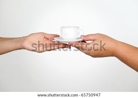 Female giving cup of coffee to another woman
