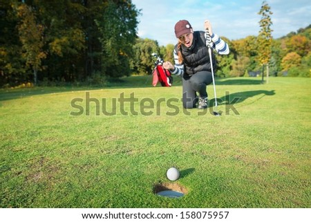Female - golf player on knees and arms raised with putter in hand in winner pose on golf green being overjoyed as golf ball drops into hole