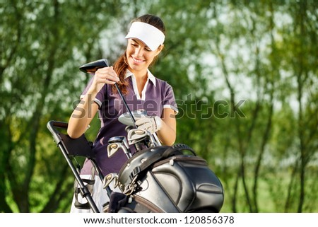 Female golf player outdoors holding a club and smiling