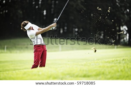 Female golf player pitching at golf course with grass in the air.