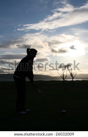 Female golfer addressing the ball