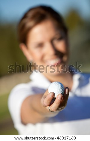 Female golfer holding a golf ball outdoors