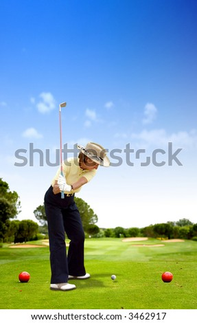 female golfer playing on a golf course on a sunny day