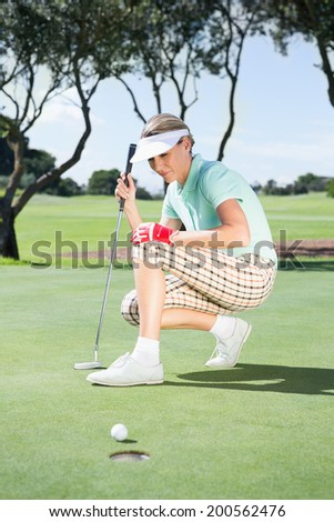 Female golfer watching her ball on putting green on a sunny day at the golf course