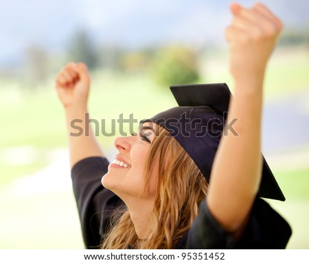 Female graduate with arms up succeeding in education - stock photo