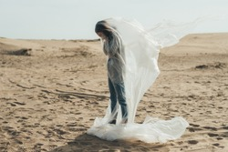 Female grief. Defocused silhouette. Isolation loneliness. Profile of hopeless woman crying covering face standing in polyethylene film flying in wind on sand desert skyline out of focus.