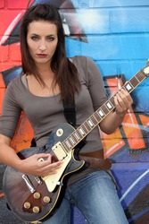 female guitar player in front of a tagged wall