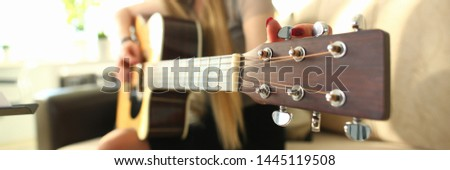 Female Guitarist Performance Music Teacher Job. Pretty Musician Tuning Acoustic Guitar Neck Playing Chords at Light Living Room. Professional Player Holding Strings Musical Instrument