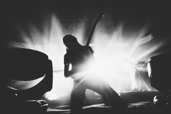 Female guitarist silhouette playing guitar solo on a stage on a knees