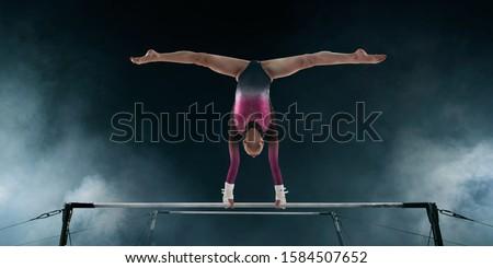 Female gymnast doing a complicated trick on gymnastic horizontal bar.