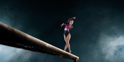 Female gymnast doing a complicated trick on gymnastics balance beam.
