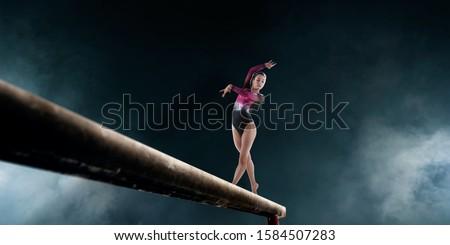 Female gymnast doing a complicated trick on gymnastics balance beam. Stockfoto ©