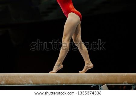 female gymnast in red leotard on balance beam on black background