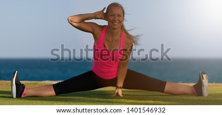 Female gymnast in sportswear, does leg split, sits on grass on ocean coast, poses in yoga, has workout exercises, stretches legs, demonstrates splits, likes fitness