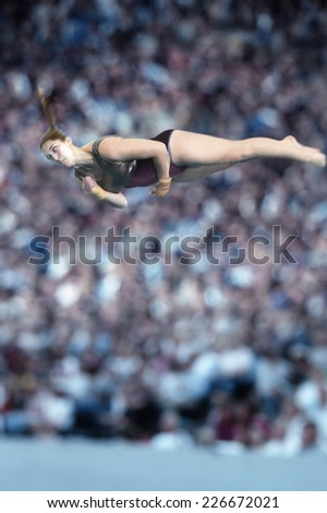 Female gymnast performing her floor exercise in front of a large crowd
